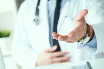 Male doctor making welcome gesture, politely inviting patient to sit down in medical office.