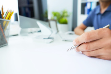 Male hand holding silver pen ready to make note in paper sheet.