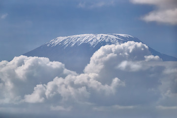 The top of the Kilimanjaro volcano, covered with snow, between clouds against a blue sky. View from Amboseli Park, Kenya.