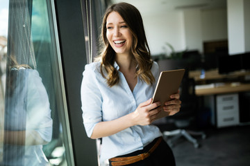 Wall Mural - Happy woman manager holding tablet and standing in modern office