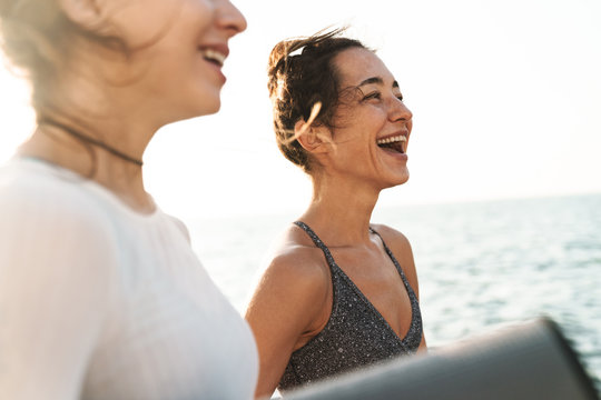 Image of happy fitness women smiling and standing with yoga mat by seaside in morning