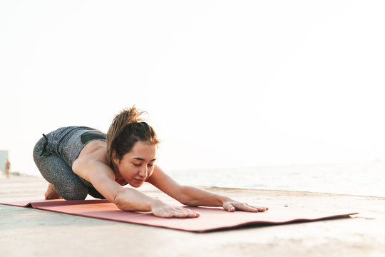 Photo of lovely sportswoman stretching her body on mat while practicing yoga by seaside in morning