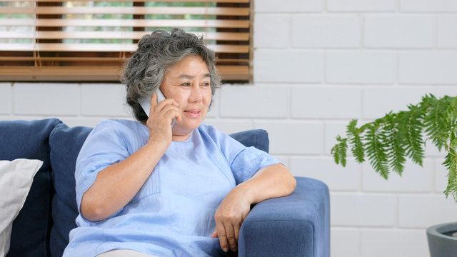 Senior asian woman talking phone while sitting in home livivg room, Asian old woman call phone with happiness, Senior, elderly, retired people and communication technology lifestyle