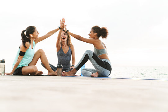 Photo of beautiful multiethnic sportswomen smiling and giving high five while sitting on yoga mats by seaside in morning