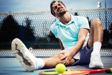 Sports injury. Young tennis player touching his knee while sitting on the tennis court