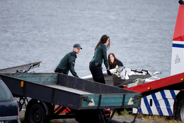 Emergency personnel unload parts of wreckage retrieved from the crash site at Ume river outside Umea