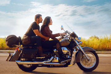 The girl rolls her boyfriend on a motorcycle. Girl is driving a motorcycle, the guy is sitting in the back Fototapete