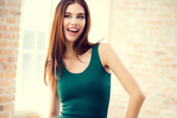 smiling girl in green clothing, indoors