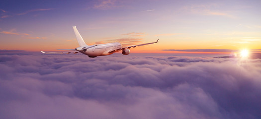 Passengers commercial airplane flying above clouds Wall mural