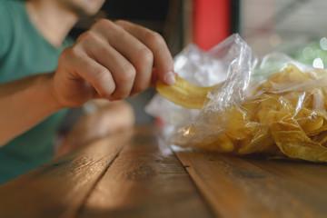 Hand picking fried crispy banana chip snack