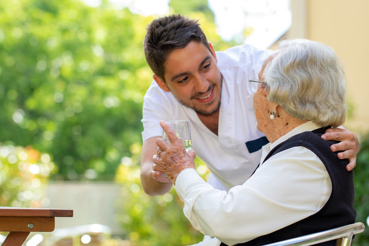 Male nurse showing affection to old woman in garden.