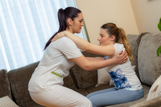 Nurse assisting young disabled patient at home.