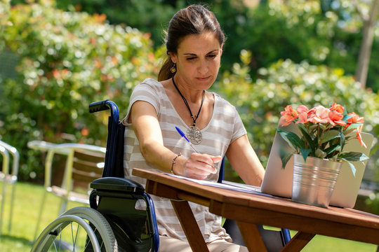 Portrait of young disabled woman in wheelchair doing paper work in garden at table.
