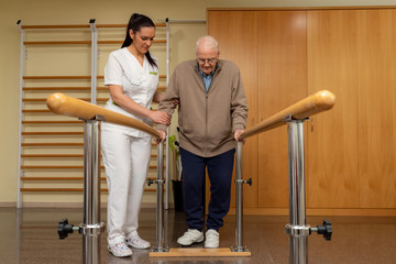 Senior stroke patient doing rehabilitation in clinic with parallel bars.