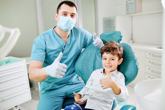 Happy dentist and child raised their thumb
