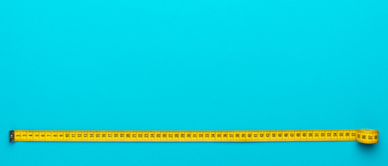 Top view of yellow soft measuring tape. Minimalist flat lay image of tape measure with metric scale over turquoise blue background. Panoramic orientation photo of tape measure with copy space.