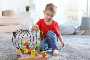 Cute child playing with bead maze on floor indoors