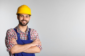 Portrait of construction worker in uniform on light background, space for text
