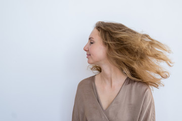 Portrait of a young beautiful girl who waves hair on a white background.