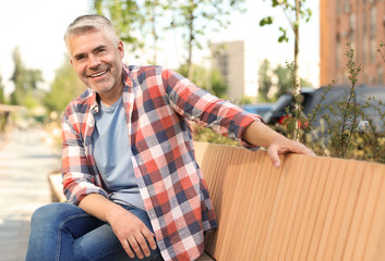 Handsome mature man on bench in park