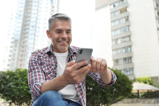 Portrait of handsome mature man using mobile phone in city center