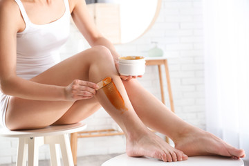 Woman doing leg epilation procedure with hot wax indoors, closeup