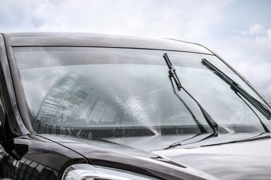 Washing car windscreen with wipers and liquid, closeup
