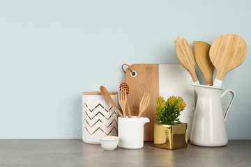 Potted plant and set of kitchenware on grey table near light wall, space for text. Modern interior design