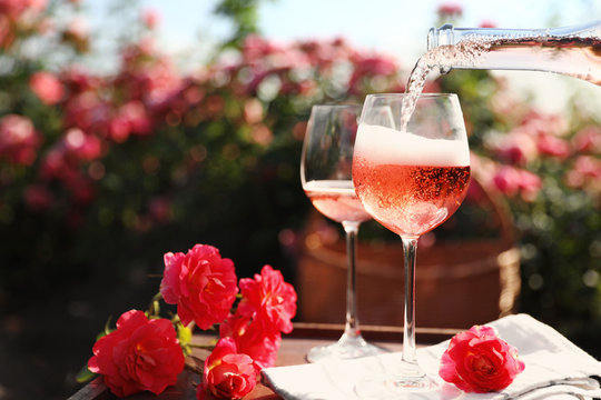 Pouring wine into glass on table in blooming rose garden. Space for text