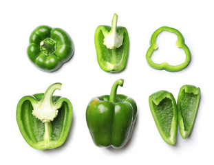 Whole and cut green bell peppers on white background, top view