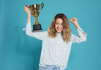 Portrait of happy young woman with gold trophy cup on blue background Wall mural
