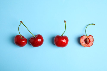 Cut and whole sweet cherries on light blue background, top view Wall mural
