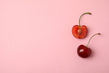 Fototapete - Cut and whole sweet cherries on pink background, top view. Space for text