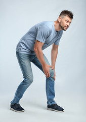Full length portrait of man having knee problems on grey background