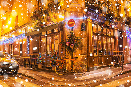 Typical Parisian cafes, decorated for Christmas holidays on a winter night in Paris, France.