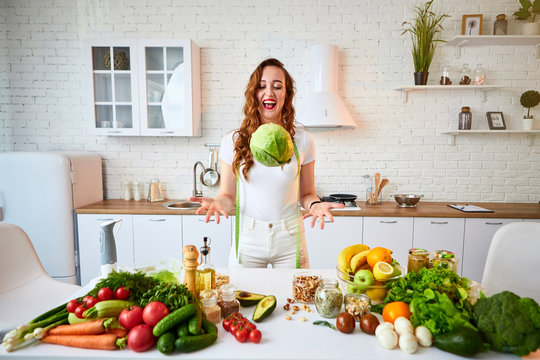 Young happy woman holding cabbage in the beautiful kitchen with green fresh ingredients indoors. Healthy food and Dieting concept. Loosing Weight
