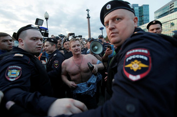 Police officers escort a far-right activist, who attempted to disturb participants of a rally in Moscow