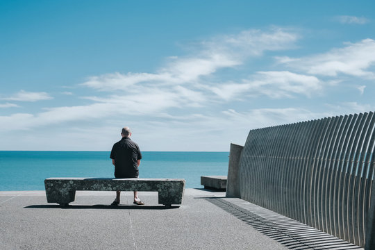 A man sitting on a wooden seat, looking out towards the sea