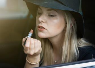 Verführerisch - hübsche, junge Frau zieht sich im Auto die Lippen mit einem Lippenstift nach