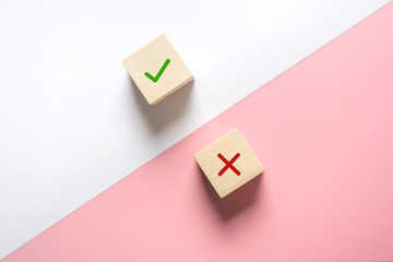 True and false symbols accept rejected for evaluation, Yes or No on wood blogs on pink and white...