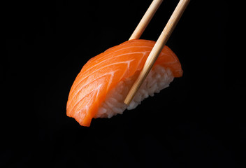 Traditional japanese nigiri sushi with salmon placed between chopsticks, separated on black background