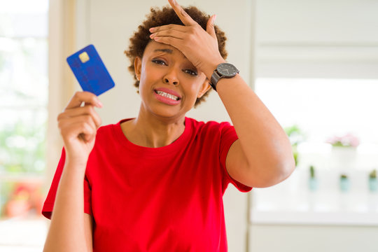 Young african american woman holding credit card stressed with hand on head, shocked with shame and surprise face, angry and frustrated. Fear and upset for mistake.