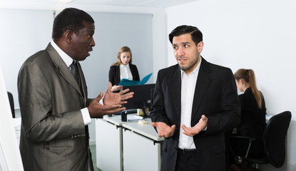 Angry man boss pointinting to misses in work to man
