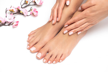 Photo sur cadre textile Pedicure Female feet and hands with nice pedicure and manicure isolated on white background.