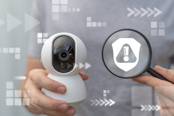 Man hold cctv camera and magnifying glass with shield exclamation icon. Violation security. Attention protection video detection fixing crime.