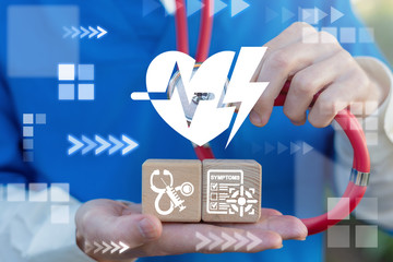 Heart Attack Symptoms Medical First Aid concept. Doctor uses stethoscope touches heart pulse and flash lightning icon and holds two wooden cubes with cardiac icons.