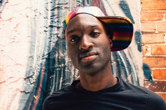Close up of man wearing rainbow baseball cap