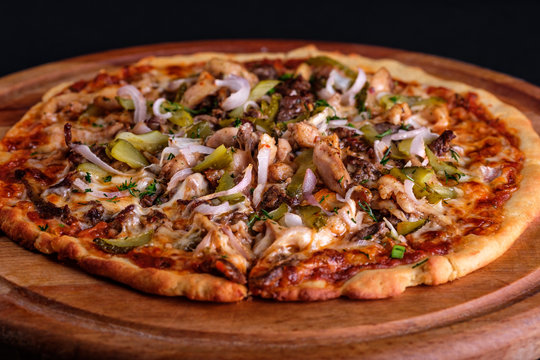 Gluten Free BBQ Chicken Pizza with lots of vegetable fillings, pickles and meat slices on a wooden board.