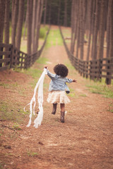Rear view of little girl running down path with streamers