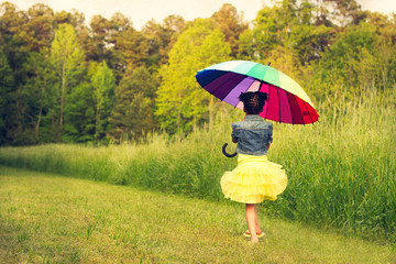 Little girl in a tutu holding a rainbow umbrella
